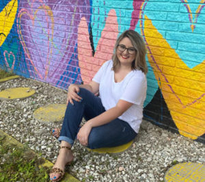 Blair Leigh sitting in front of a colorful mural